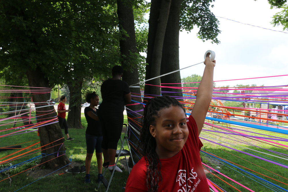 Kiarra Wallace uses flagging tape to create colorful walls between trees in the park.