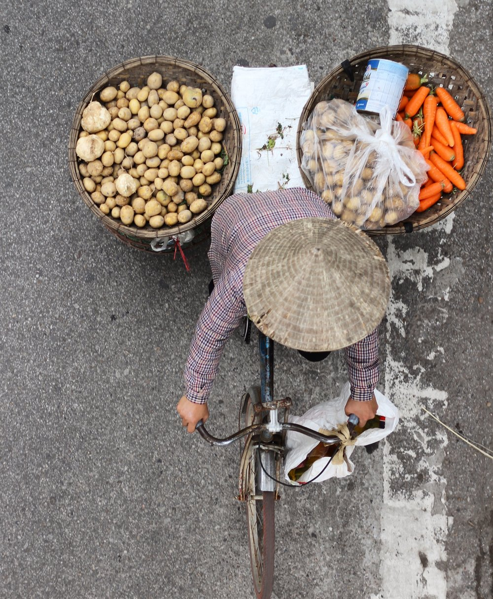 A woman biking through Hanoi with her vegetables.