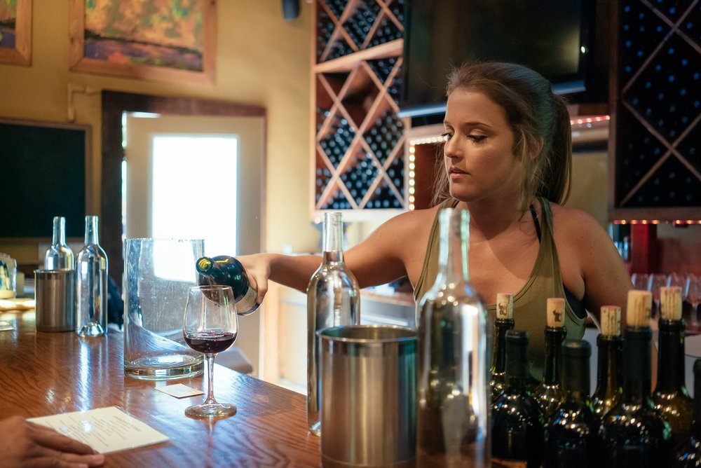woman-pouring-a-cup-of-wine-at-winery