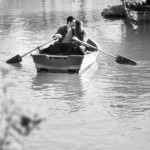 a couple kissing in a paddle boat