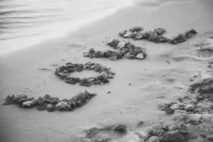 """love"" spelled out in rocks on the beach"