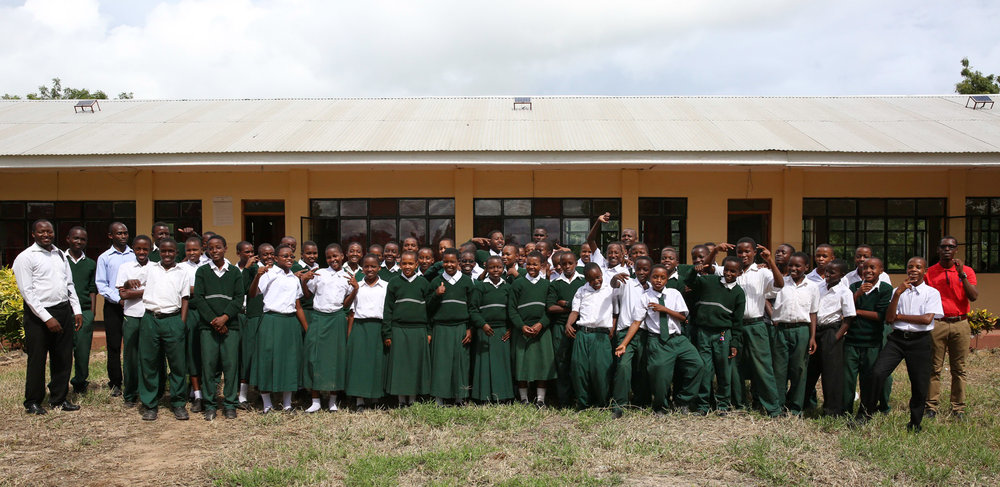Mtakuja Form I, the first class in the world to use an all-NGL curriculum, poses after class with their six mentors.
