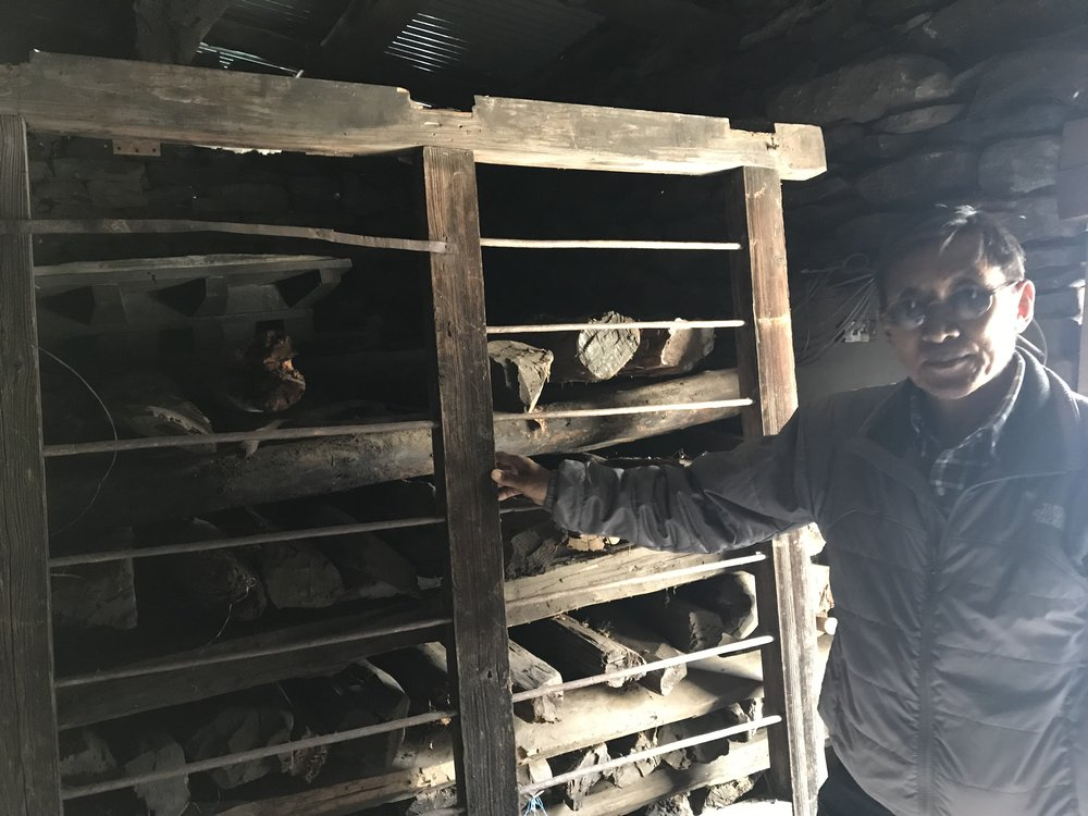Ground floor of the Sherpa Heritage House: Pertemba standing in front of storage racks holding saved 350 year old timbers and beams.