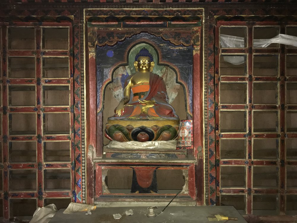 Ancient statue of Buddha in the Gompa with empty prayer scroll storage racks.