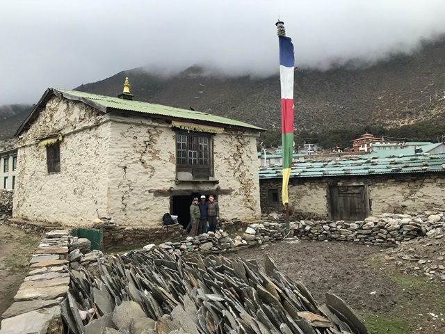 Outside the Gompa and Sherpa Heritage House in Spring 2018. The image clearly shows the cracked and damaged walls of the Gompa and to the right the Heritage House. Salvaged stones and slates are in the foreground.