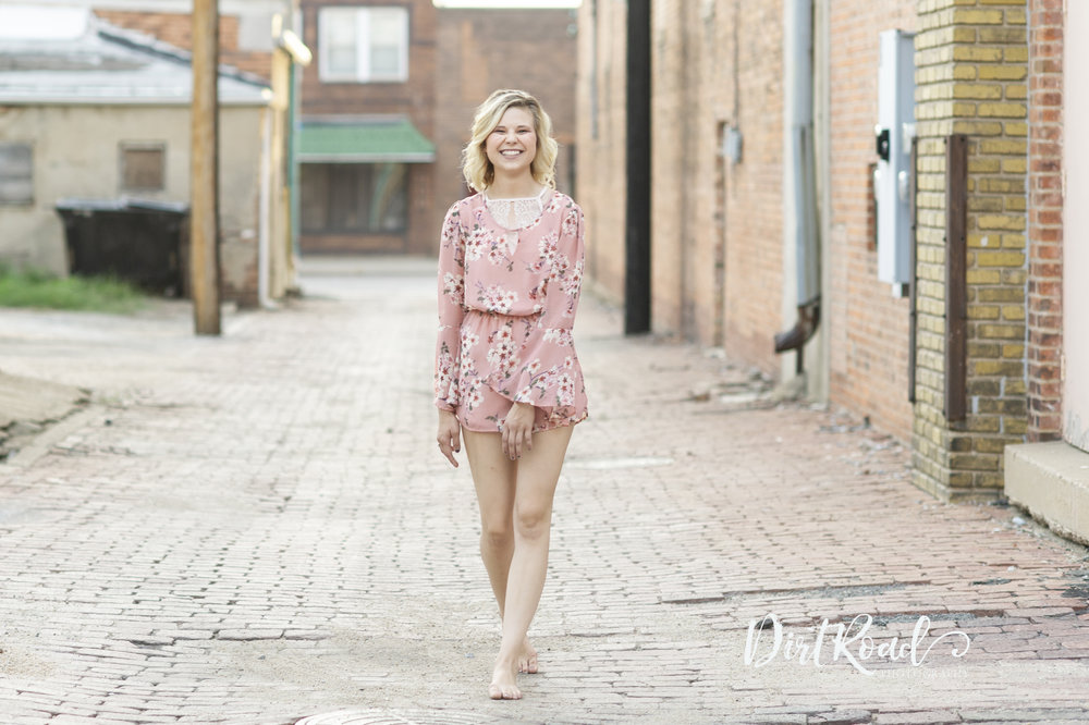 dirt-road-photography-fairbury-nebraska-southeast-photographer-family-farm-cows-grass-sunshine-sunflare-haybales-girl-senior-high-school-wilber-southeast-nebraska-photgrapher-photography-alley-downtown-urban-romper-dress-girl-walking