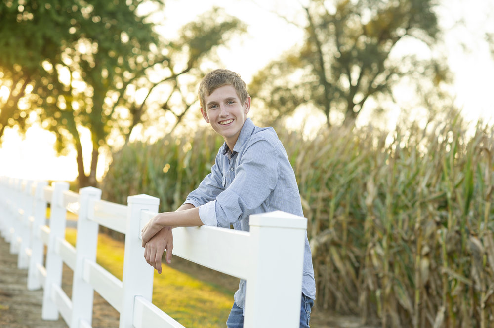 dirt-road-photography-kelsey-nerud-wilber-nebraska-dorchester-southeast-photographer-senior-farm-grass-sunshine-sunflare-sunset-guy-boy-senior-high-school-wilber-southeast-nebraska-photgrapher-photography-green-grass-cornfield-corn-white-fence-smiling