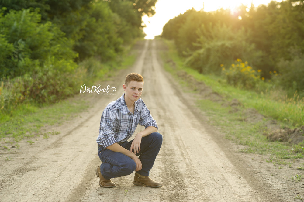 dirt-road-photography-kelsey-nerud-wilber-nebraska-southeast-photographer-senior-farm-grass-sunshine-sunflare-sunset-guy-boy-senior-high-school-wilber-clatonia-southeast-nebraska-photgrapher-photography-green-grass-plaid-shirt-jeans-boots-belt-buckle-wrangler-road-sunset-sunshine-pius-x-high-school