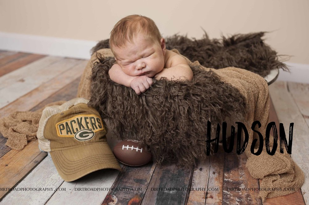 newborn session with best newborn nebraska photographer kelsey homolka nerud picture of baby with packers football hat on a wood floor. dirt road photography located near wilber nebraska is a newborn portrait photographer