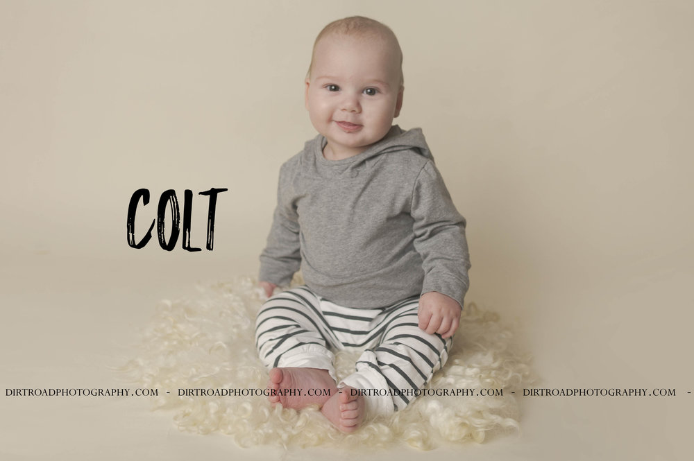 picture of six month old baby boy in outfit from amazon of gray shirt with hoody and black and white striped pants sitting on gray faux fur mohair curls with bone seamless backdrop paper dirt road photography by kelsey homolka nerud photographer located near wilber nebraska.