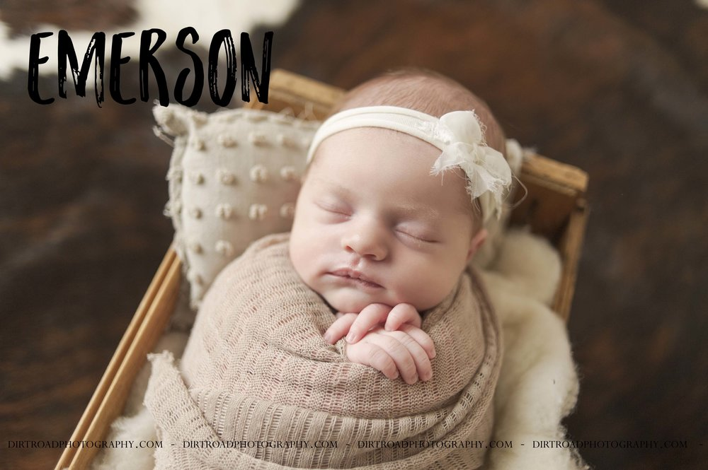 emerson rose picture of newborn infant baby girl in wooden box with white fluffy layer underneath and cream colored pillow wrapped in swaddle that is light brown colored wearing a white headband bow. Cowhide rug underneath box that baby is sitting on. dirt road photography by kelsey homolka nerud photographer located near wilber nebraska.
