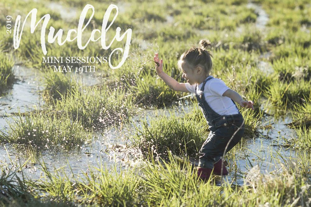 Muddy Mini Sessions held near Wilber, Nebraska with Photographer Kelsey Homolka Nerud from Dirt Road Photography. Picture of three year old girl splashing water into the air at sunset wearing jean overalls, pink mud boots and a white t-shirt. Toddler girl in photos of Nebraska Child Photographer.