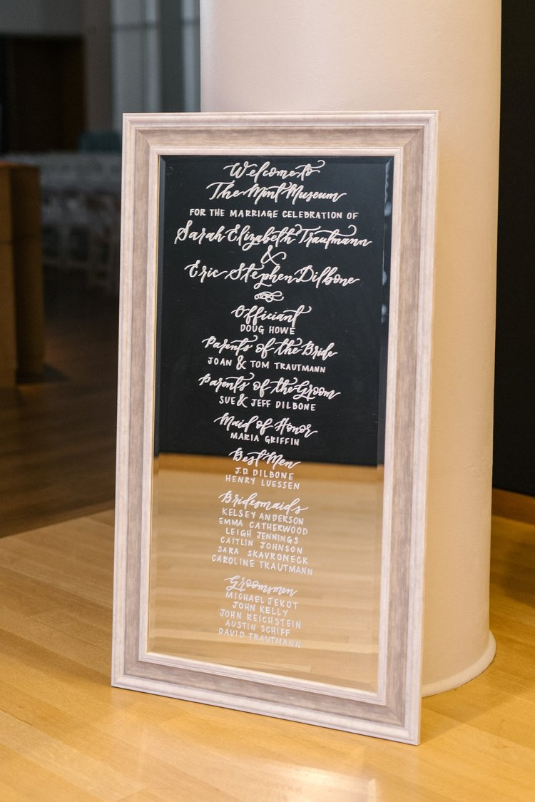 Ceremony program on a mirror for Sarah & Eric's wedding