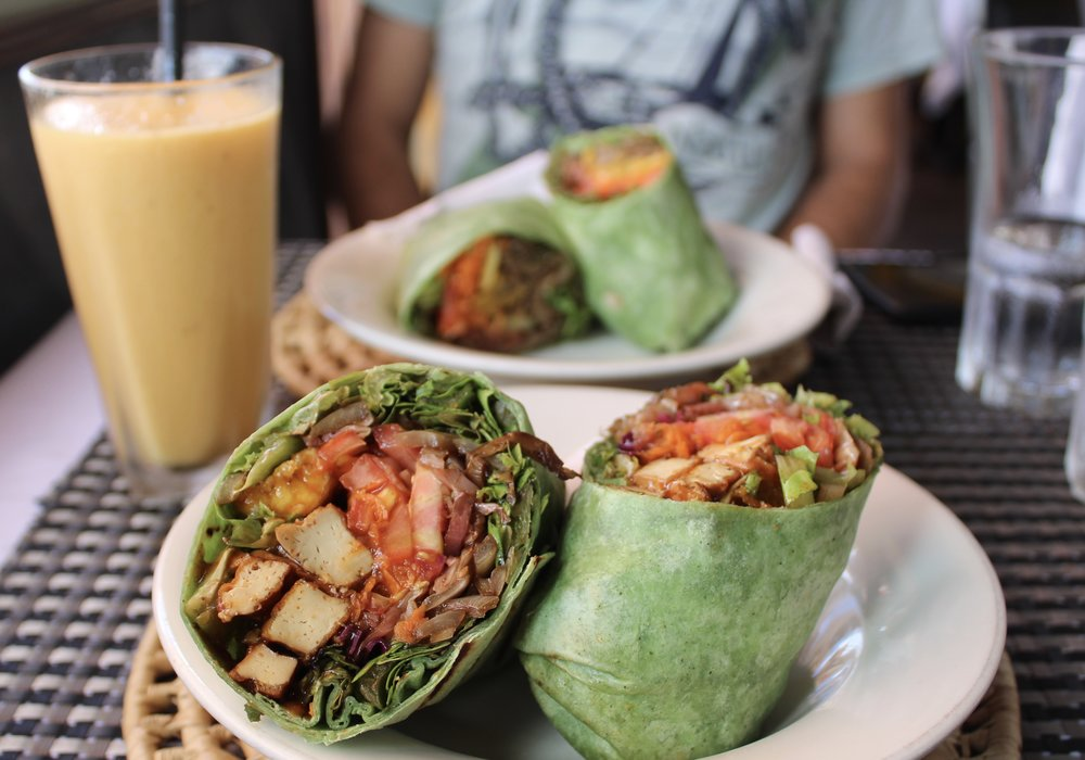 """BBQ """"chickin"""" wrap $14 USD in foreground. Deluxe veggie wrap $12 USD and vegan mango lassie smoothie $6 USD in background."""