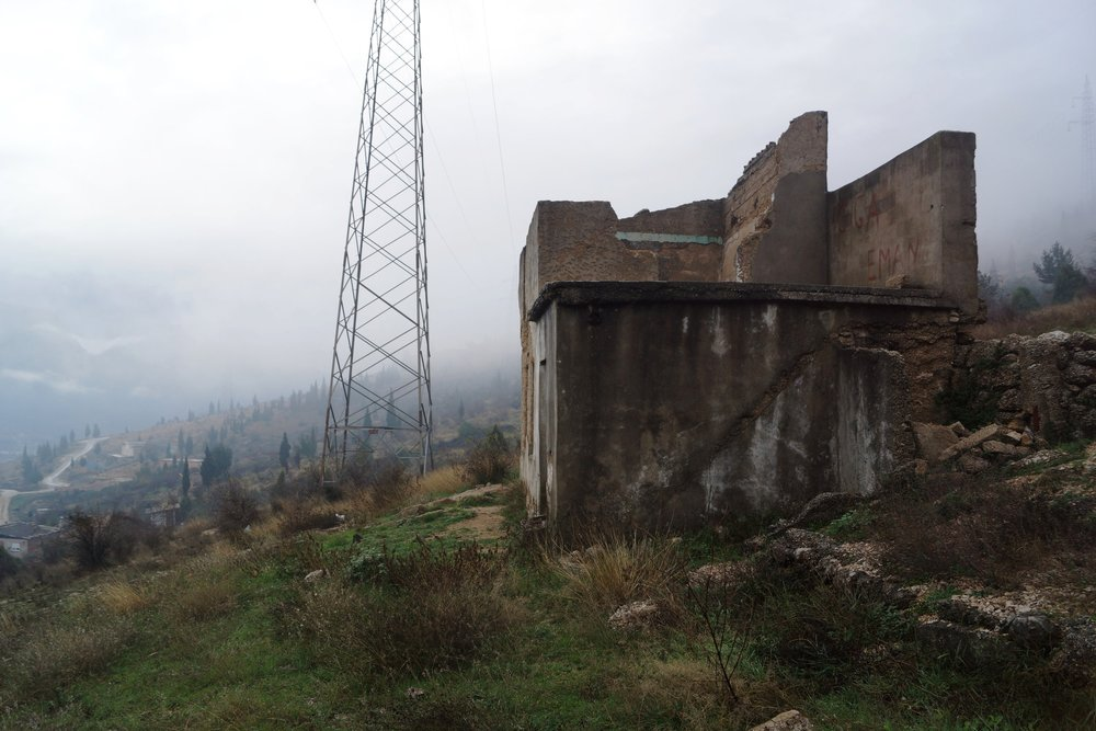 A bomb shelter overlooking Mostar from the east, as a heavy fog sets it. War-torn buildings like this are left to decay all over the city, some 25 years after a ceasefire came into force.