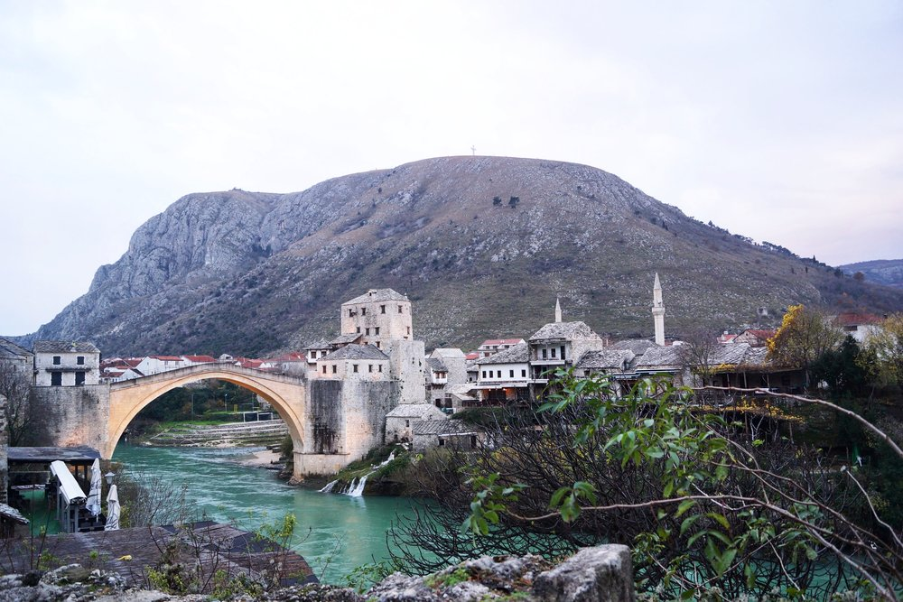 The Stari Most bridge is overlooked in the distance by a towering 30 meter cross, only visible from East Mostar - the city's Muslim district.