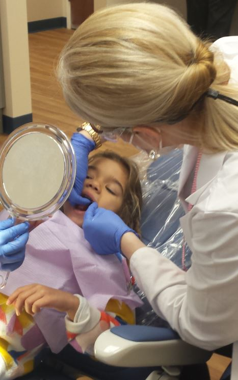 Dr. Elsie Hinz shows her patient, Nalea Tylor, how to floss.