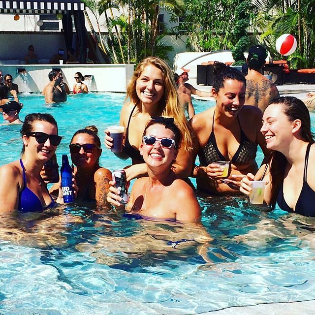 Young women enjoying beers and cocktails in the pool, smiling
