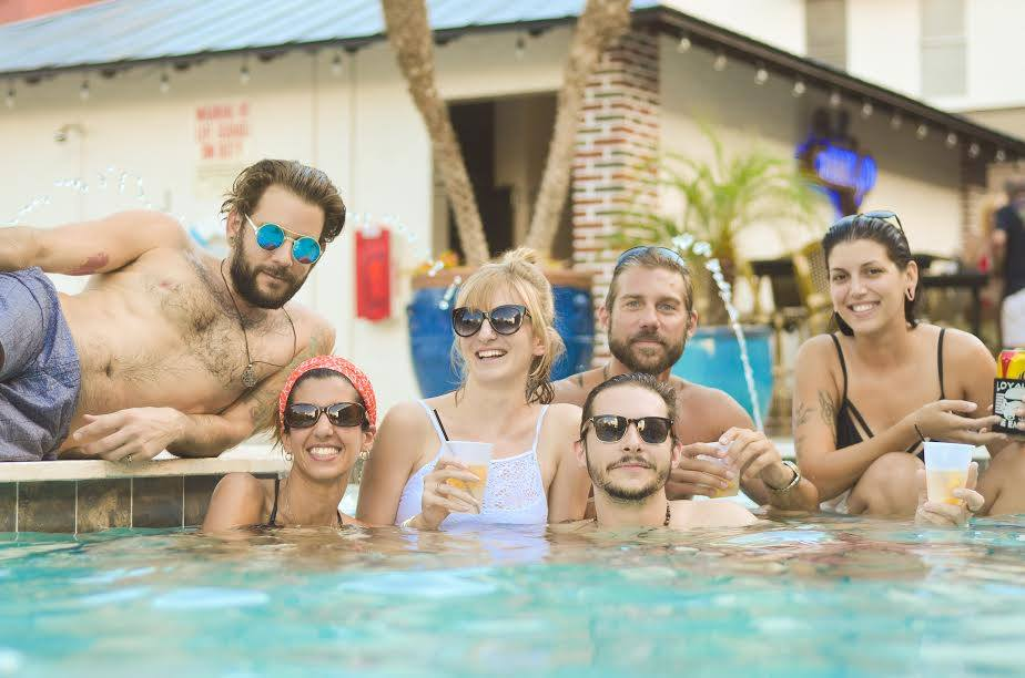 Friends enjoying some drinks in the pool and smiling