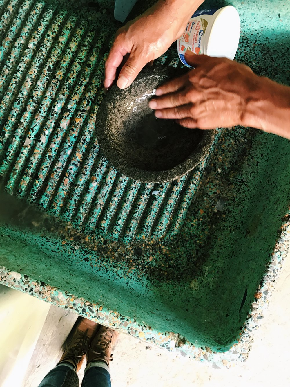 I bought a  molcajete      (a stone with a bowl carved into it used to grind things and make salsa) to bring home with me and here is my dad prepping it for me to make sure my first salsa in it isn't filled with a bunch of little rock (which is exactly what would have happened! Ha!)