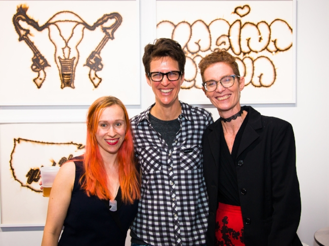 Your Body Is a Battleground  curator Wendy Vogel, MSNBC's Rachel Maddow, and VOLTA Artistic Director and co-founder Amanda Coulson pose in front of match-burn compositions by Melissa Vandenberg (presented by beta pictoris gallery / Maus Contemporary, Birmingham)