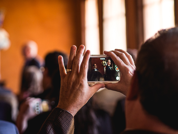 Portrait of someone taking a photo of a wedding with their cell phone, taken by Orlando Pet Photography
