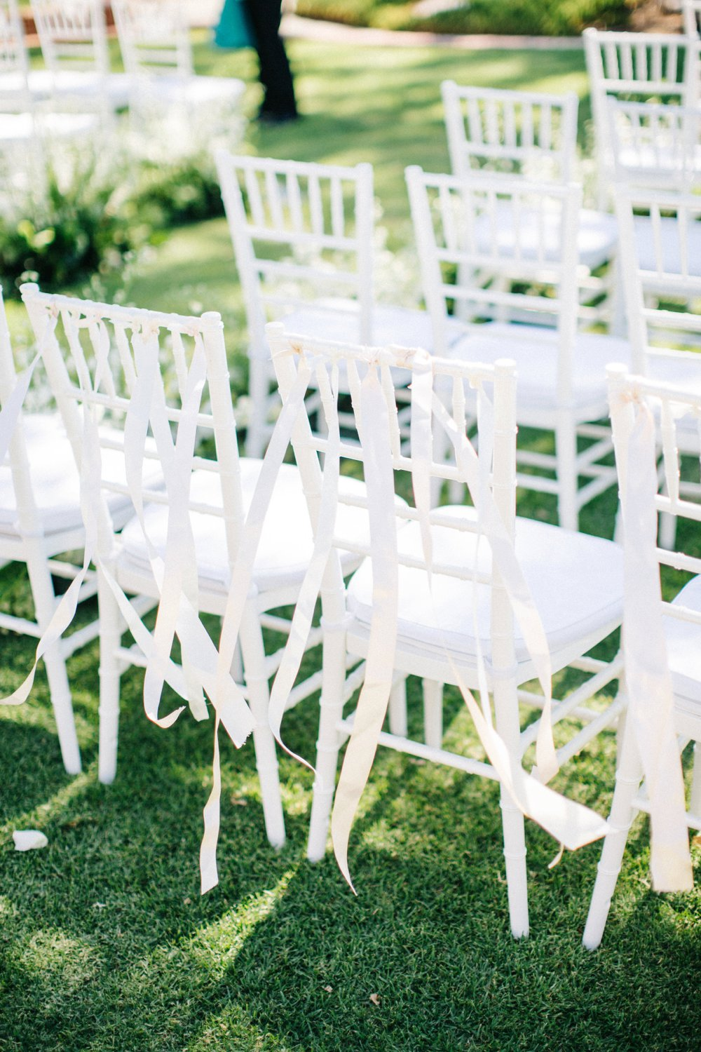 White Tiffany Chairs dressed with white ribbons