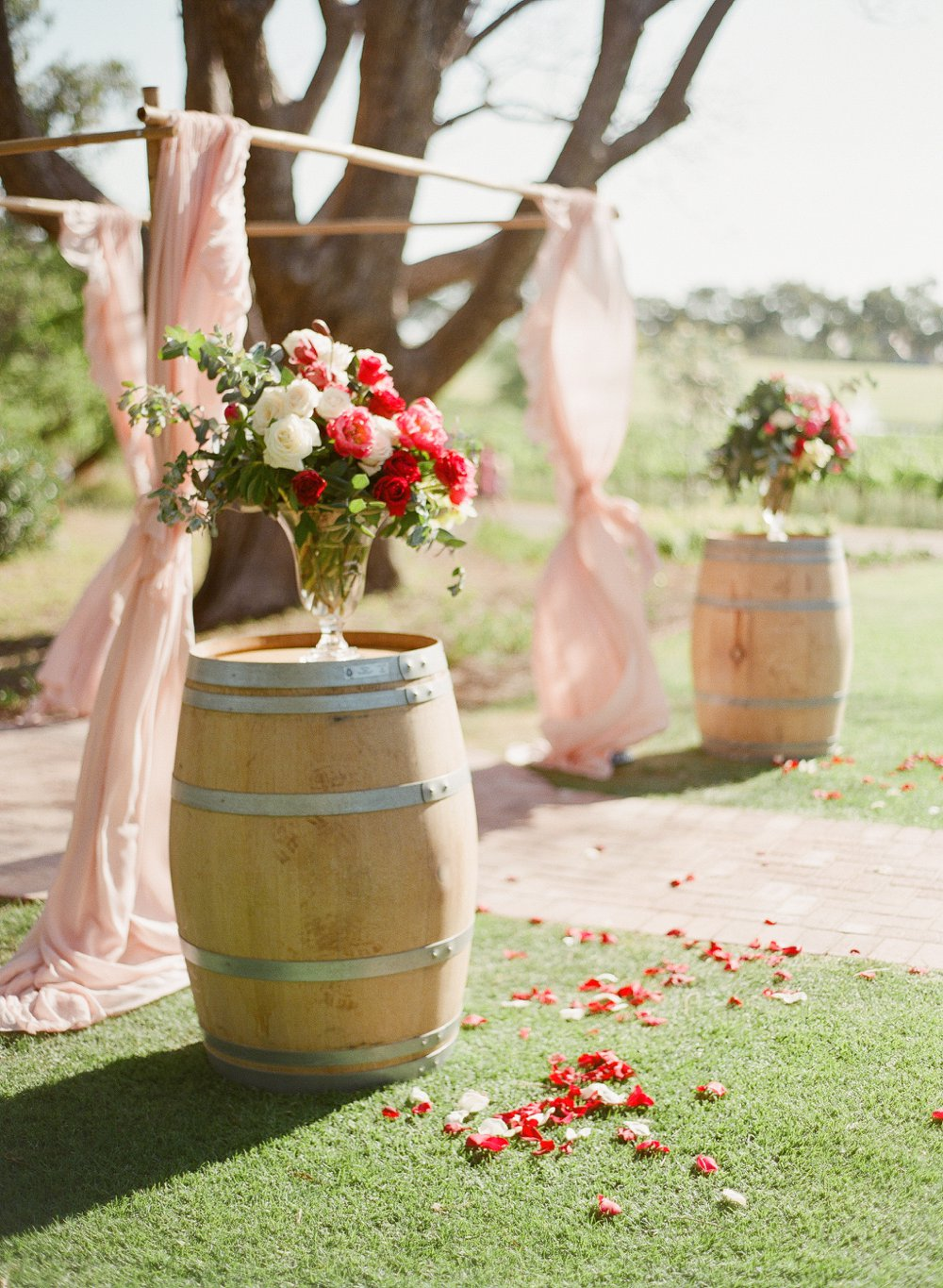 Bamboo canopy with dusty pink curtains and flowers by Flower Talk