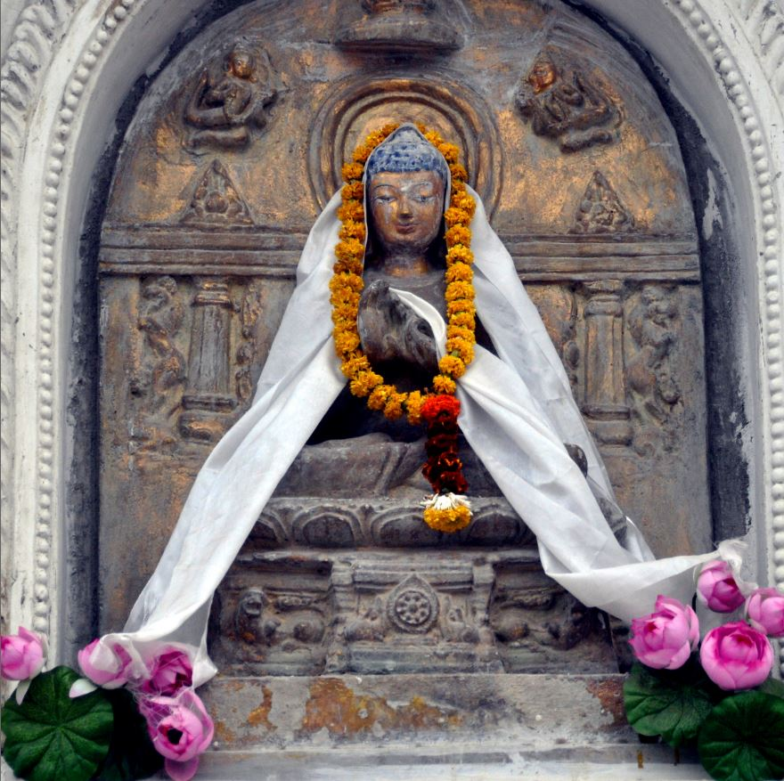 Buddha image with scarf and flowers at the Mahabodhi Stupa, Bodhgaya.JPG