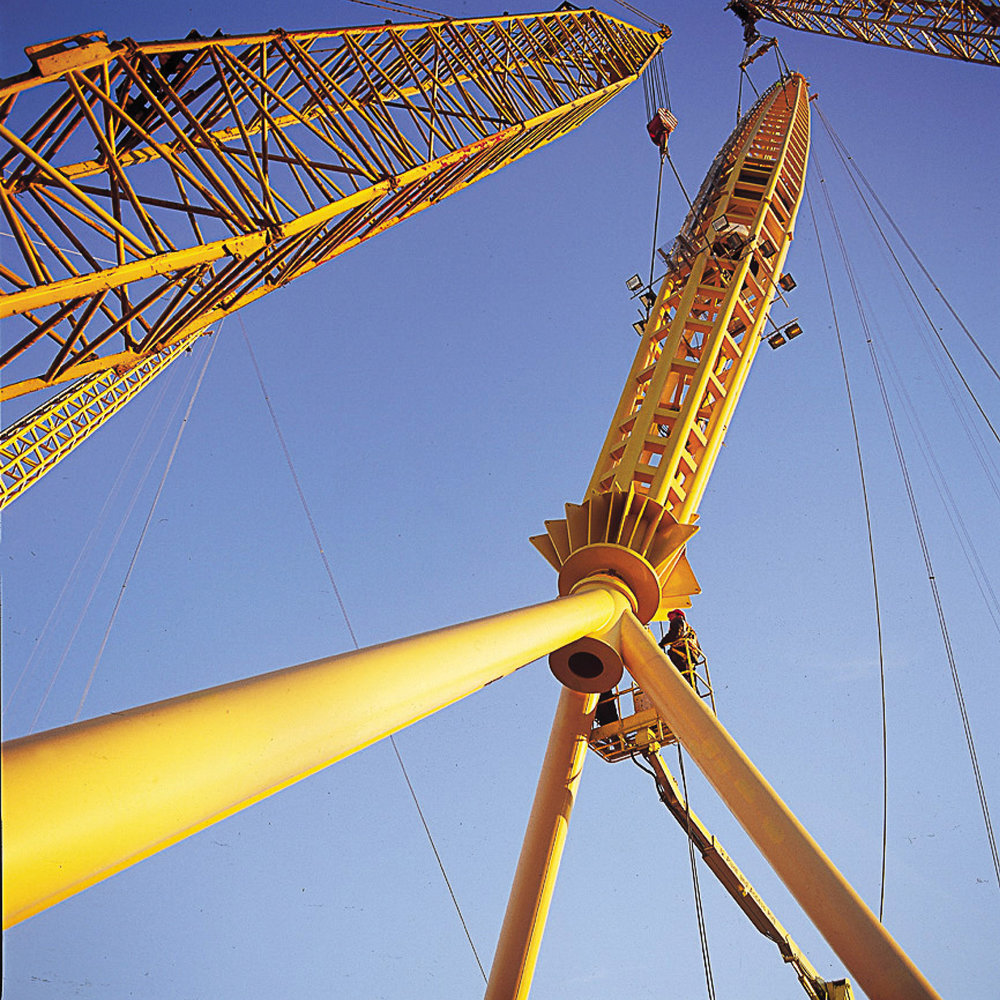 Under construction photograph of the yellow steel pylonds being raised into position to form the structure of the Millenniumk Dome.