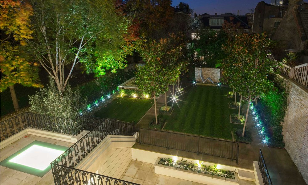 Night time photograph of the landscaped garden above the underground swimming pool.