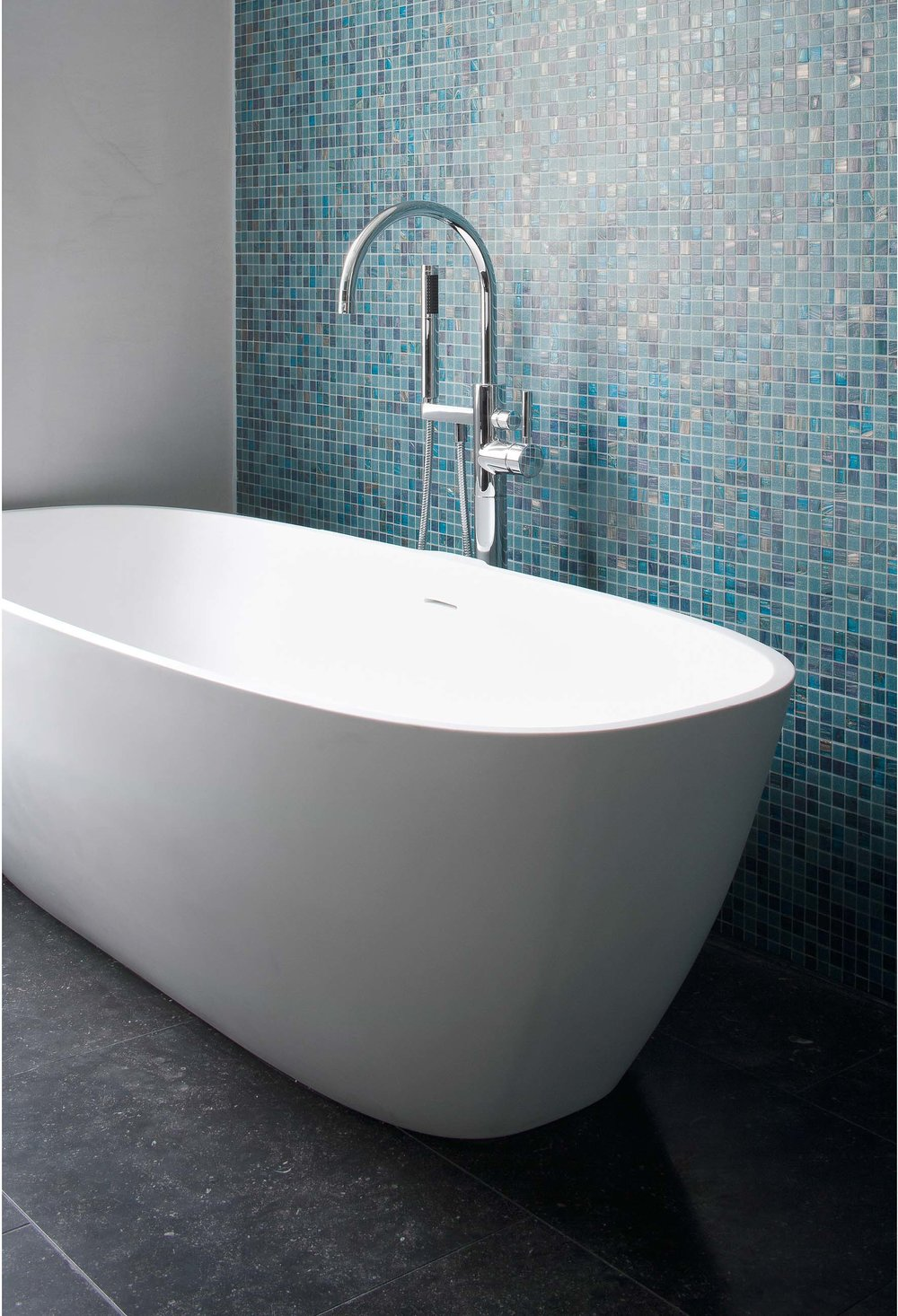 The bath in the master bathroom. Set on luxuary tiles with a turquoise tiled back walll.