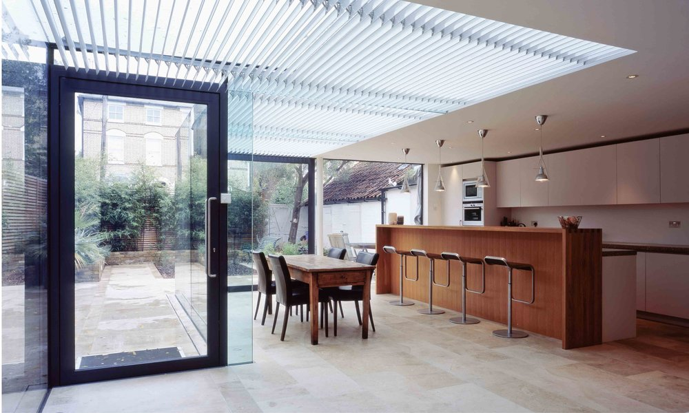 This modern glass extension brings the kitchen and garden together. Mechanical louvres track the sun reduce solar glare. The extension is construction entirely from glass, including the beams and columns.