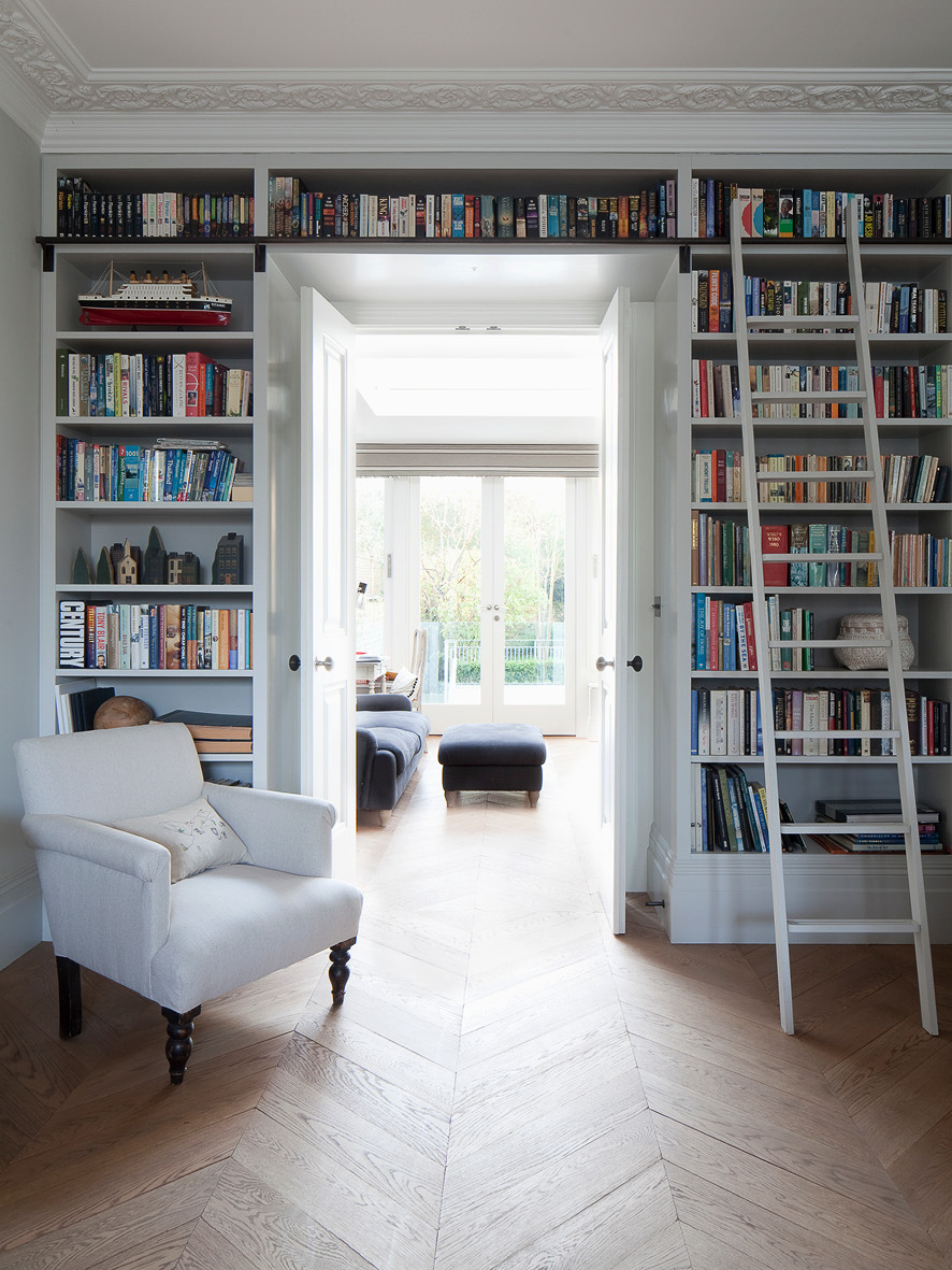 The library. Herringbone wooden floor boards connect seamless connect this room to the living room through a beautifully detailed set of double doors.