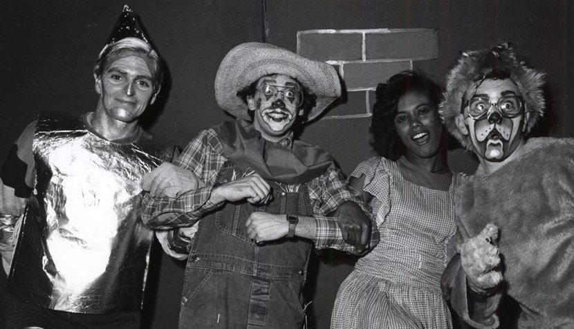 "A production number on ""The Wizard of Oz"" featured Bernie Feord '88 as the Tin Man (Professor Charles Goetz); Fred Wagner '87 as the Scarecrow (Professor Michael Dooley); Mikki Graves (now Wasler) '88 as Dorothy (Professor Mildred Robinson); Mike Callahan '88 as the Lion (Professor Cal Woodard). Photo Credit law.virginia.edu."