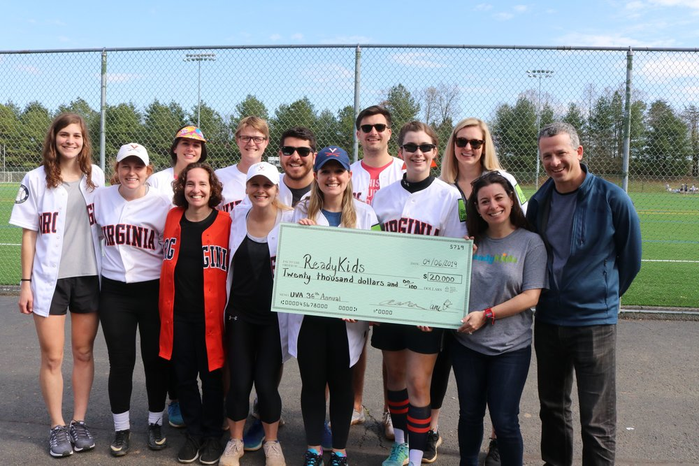 A group of students from the North Grounds Softball League along with Dean Risa Goluboff and Professor Rick Schragger presented a donation check to ReadyKids from the proceeds of the 36th Annual Softball Invitational. Photo credit Mary Wood Schmalzl.