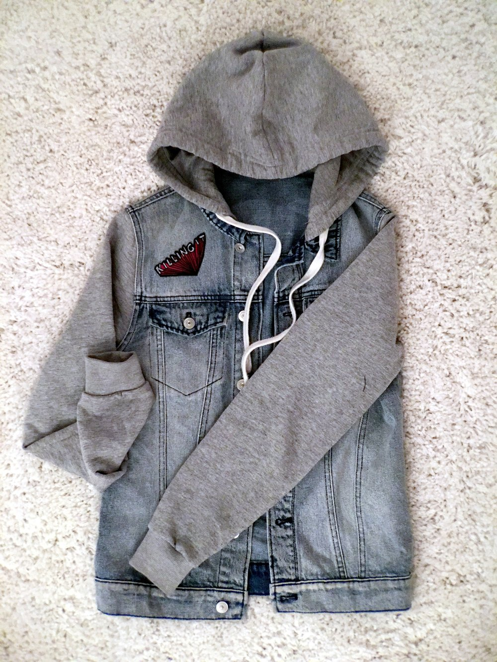 Blue denim Jacket with grey sweater sleeves and killing it iron-on patch