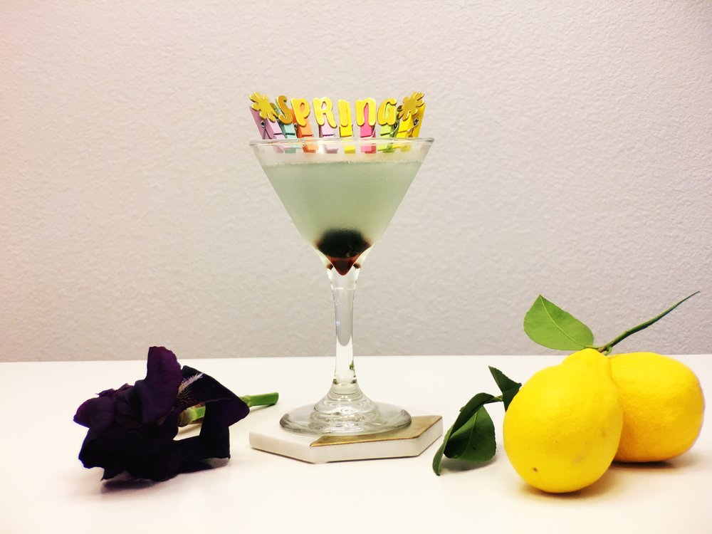 The Aviation Cocktail has blue color with a Luxardo Maraschino Cherry Garnish that drops to the bottom in a martini glass.
