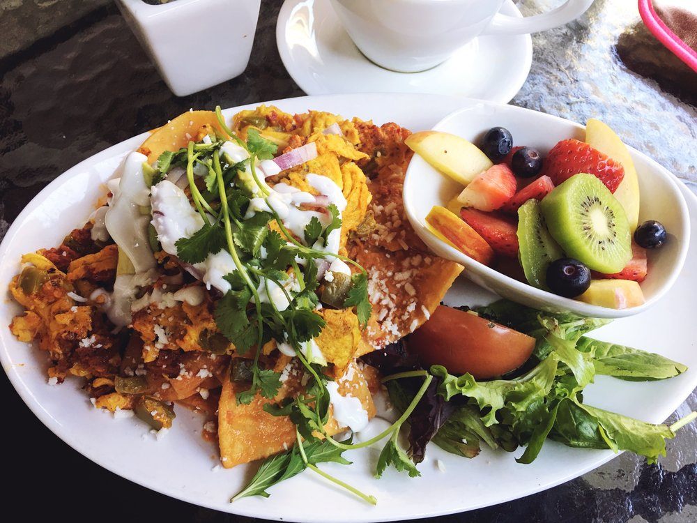 Chorizo and Chilaquiles (fried tortillas) and a side of fruit from La Mo Cafe