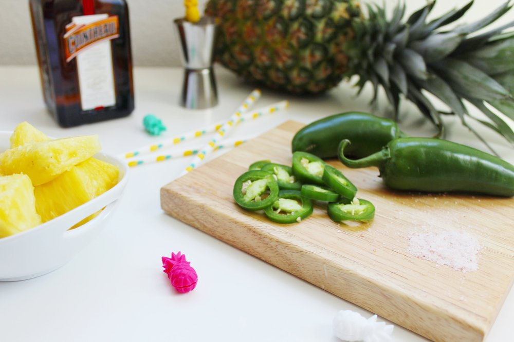 Wood Cutting Board with Sliced Jalapeños. A pinch of salt and sliced pineapple chunks. Target pineapple drink markers and pineapple paper straws.