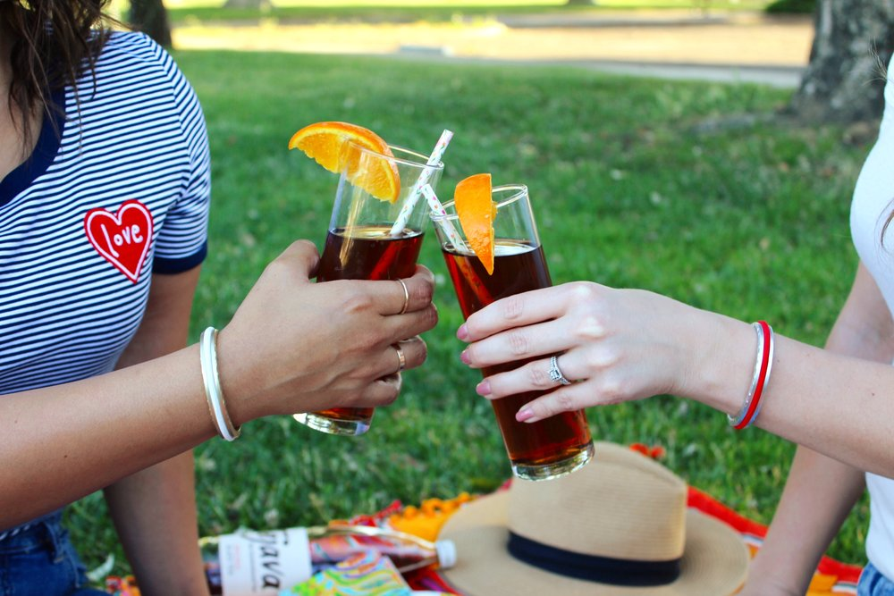 Cheers with Tejava Black Tea garnished with an orange in the park.