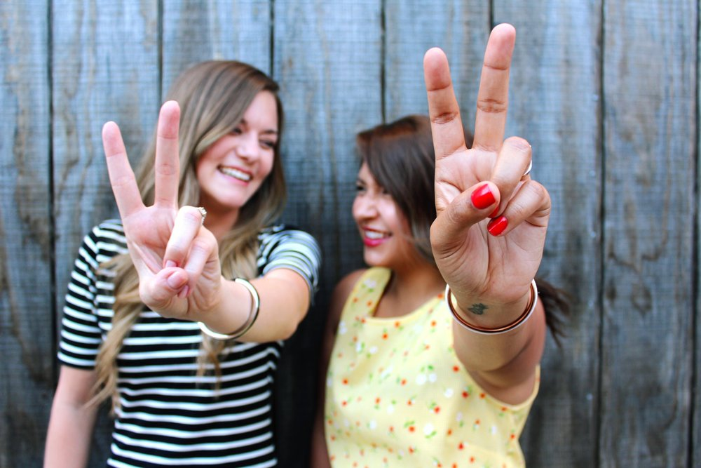 BFF's saying Peace out. Yellow Floral Dress and Stripe Dress.