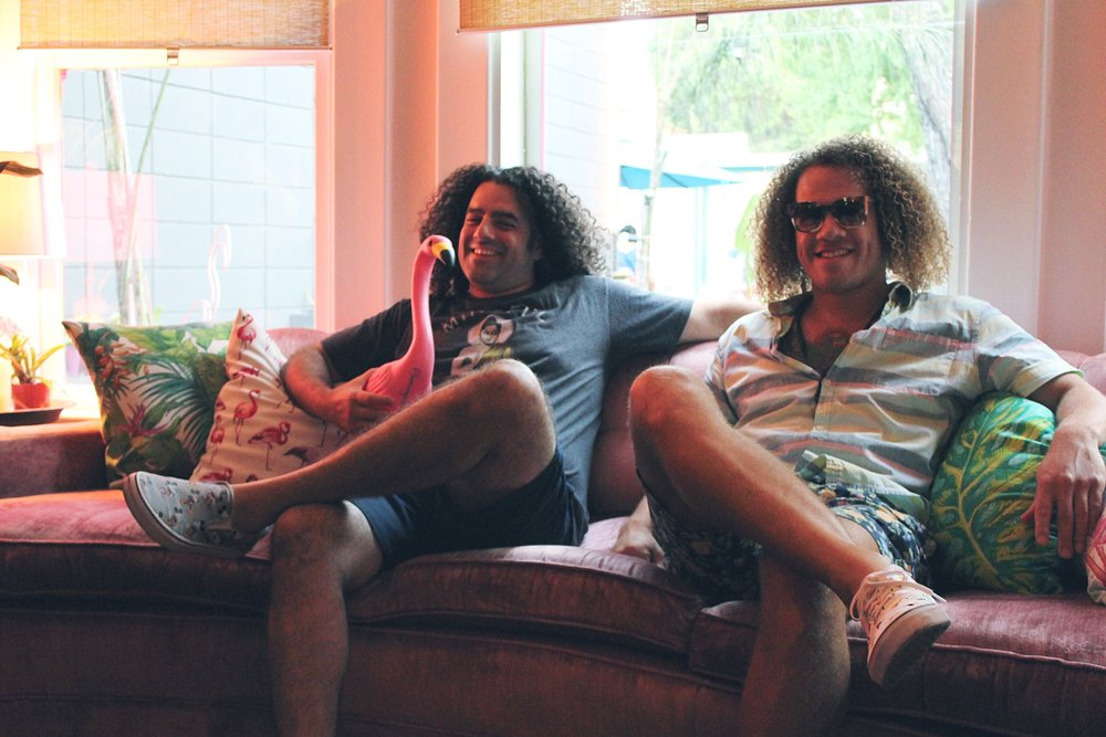 Guys with long curly hair, pink velvet couch, flamingo pillow, owners of the Flamingo House Social Club