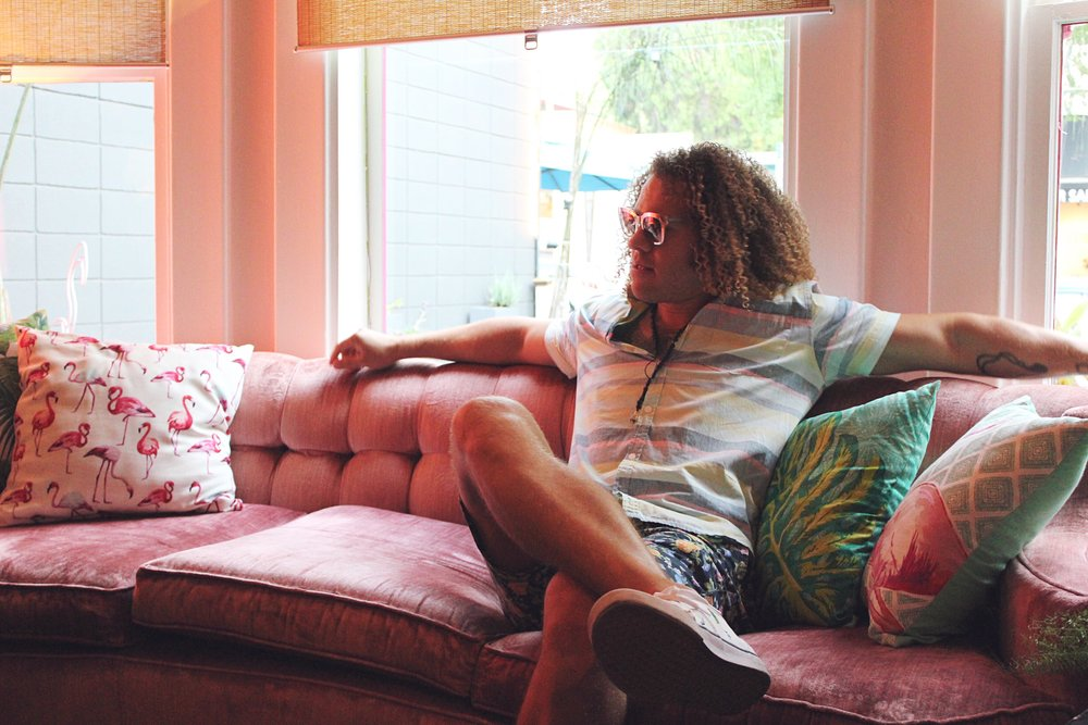Matt Bryd part owner of Flamingo House Social Club sitting on a pink velvet couch