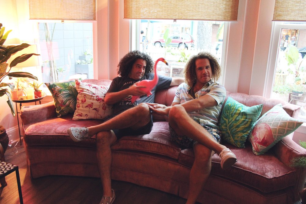 The owners of Flamingo House Social Club sitting on a pink velvet couch holding a lawn flamingo