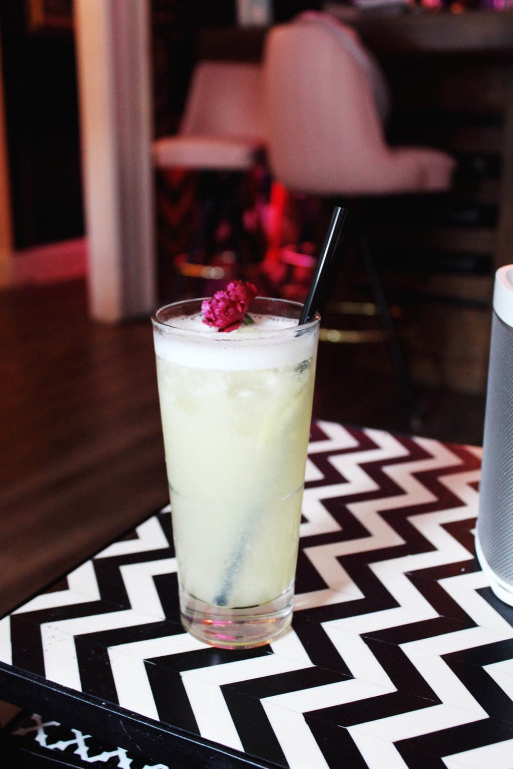Pineapple Jalapeño Margarita garnished with a purple flower on a chevron side table from Flamingo House Social Club