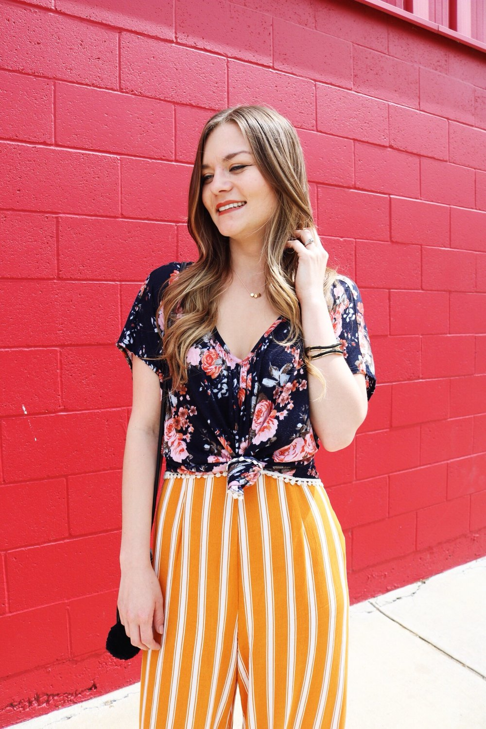 Yellow striped pants with navy floral top. Gold accessories
