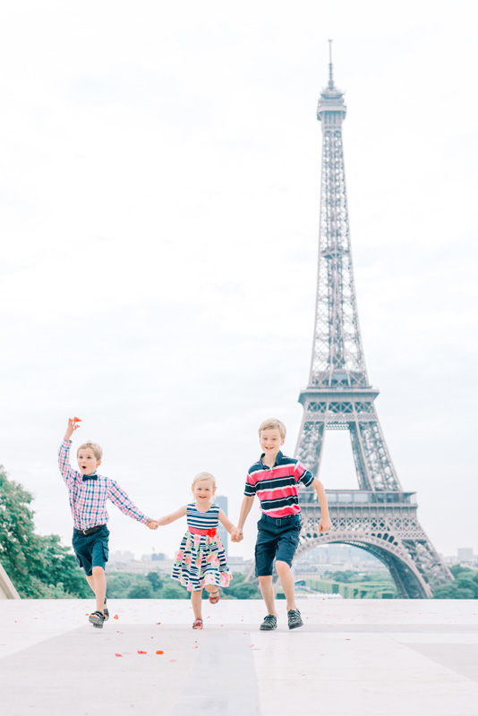 paris photographer - family photo shoot with kids having fun at the Eiffel Tower in Paris