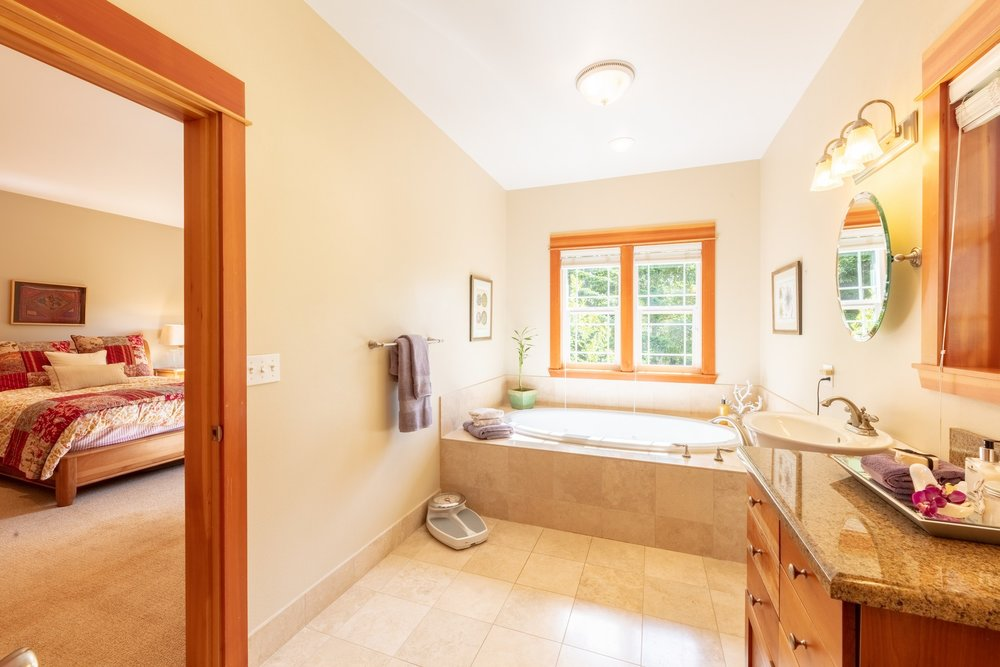The  spacious  master  bathroom  is  tiled  throughout,  with  huge  soaking  bathtub,  cherry  cabinets,  double  sinks,  large  shower  and  separate  water  closet.