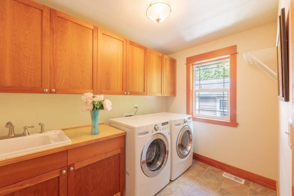 The  laundry  room  features  cherry  cabinets  with  generous  linen  storage,  newer  LG  washer  and  dryer  and  utility  sink.